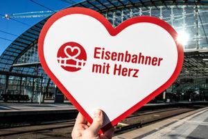 Logo auf Herz wird vor Bahnhof gehalten
